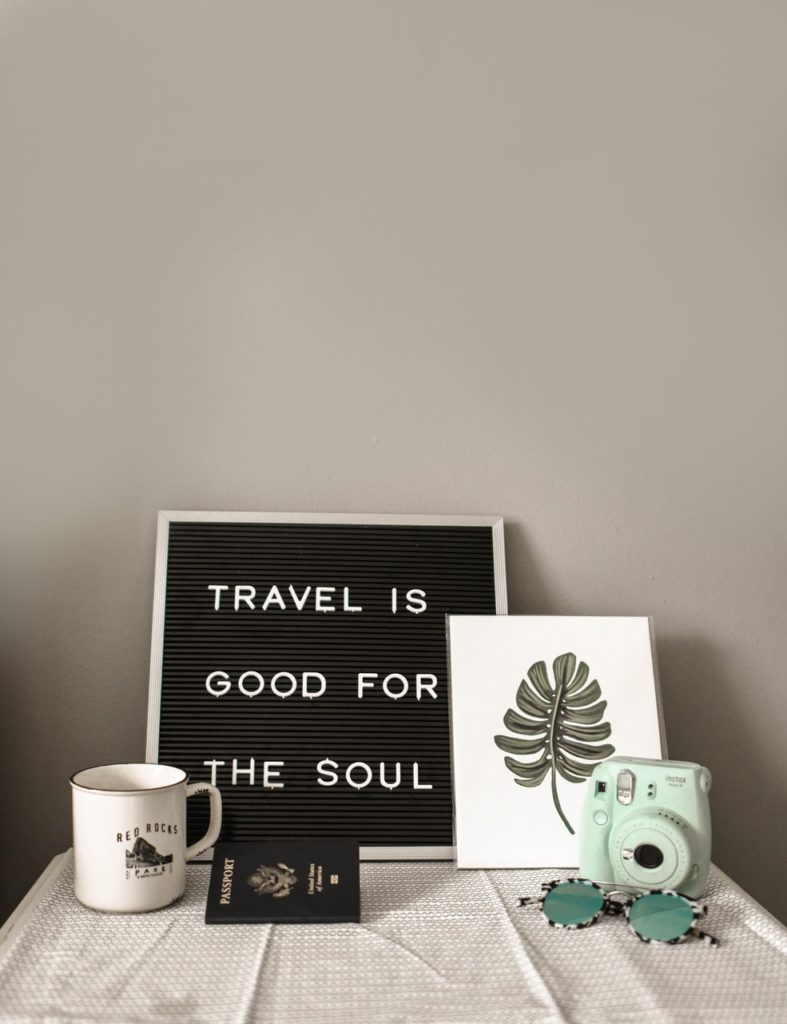 "A letter board that says ""Travel is good for the soul"". It's neatly placed next a mug, passport, photo, and camera."